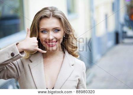 Beautiful woman making a call me gesture