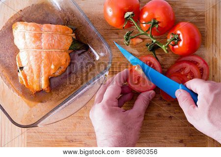 Chef Slicing Tomatoes To Accompany Salmon