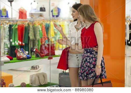 Two young beautiful girls standing at the storefront with shopping bags