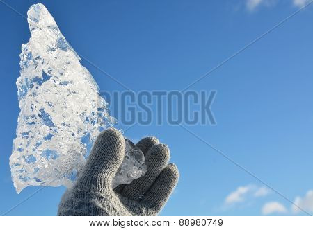 Crystal Clear Ice Piece At The Hand With Blue Sky Background