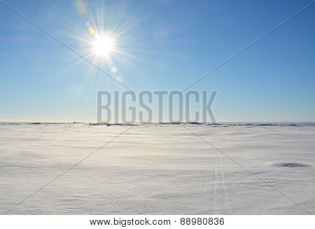 Polar Landscape- Frozen Sea Shore With Sun And Ski Tracks