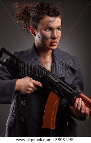female killer with AK-74 (Kalashnikov) assault rifle in studio. With dirty face, blood and wound.