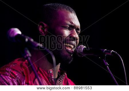 Black man singing and playing guitar