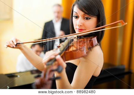 Woman playing the violin with a pianist