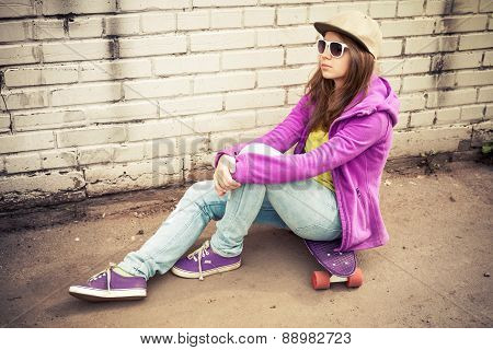 Girl In Jeans, Cap And Sunglasses Sits On A Skateboard