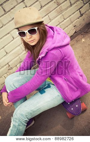 Blond Girl In Cap And Sunglasses Sits On A Skateboard