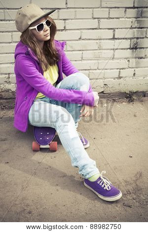 Girl In Jeans And Sunglasses Sits On Her Skateboard