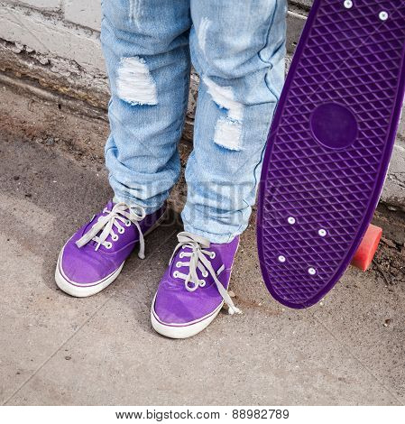 Teenager In Blue Jeans Stands With Skateboard