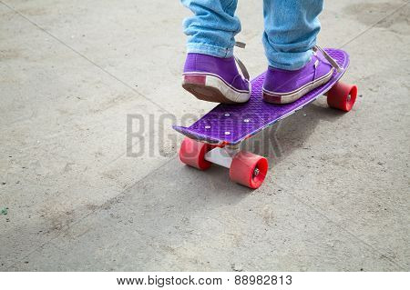 Riding Skateboarder Feet In Jeans And Gumshoes