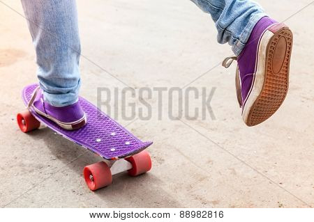 Feet Of Riding Skateboarder In Jeans And Gumshoes