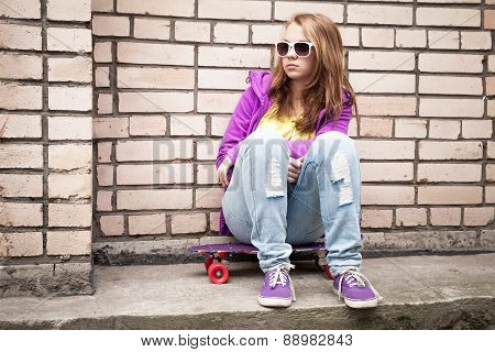Blond Teenage Girl In A Sunglasses With Skateboard
