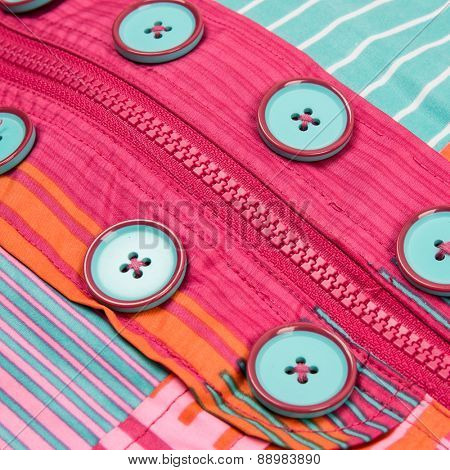 Close up zipper and button on a colorful background