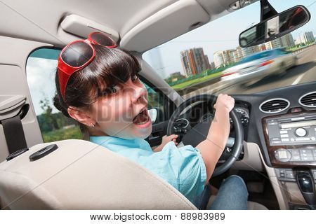 Woman in panic behind the wheel of the car. Driving lessons The woman behind the wheel..