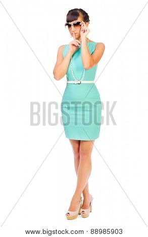 Glamorous girl in turquoise dress shows quiet gesture isolated