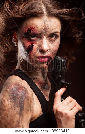Beautiful sexy girl with gun. Posing in studio. With blood on face.