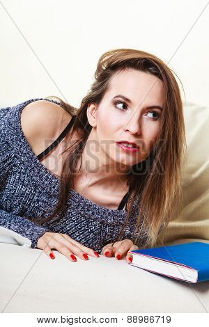 Woman Relaxing After Lunch With Book On Couch