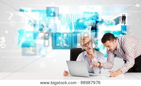 Business persons at desk with modern blue tech images at background