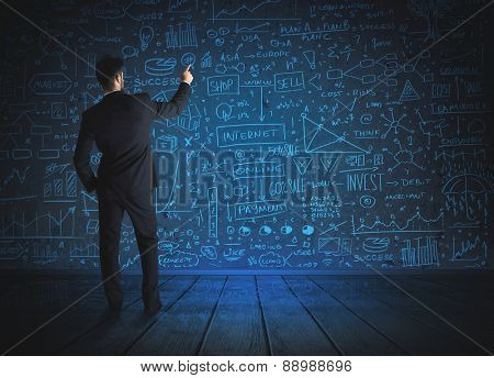 Businessman drawing business schemes on glass wall