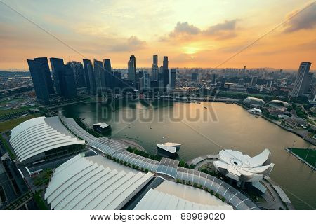 Singapore rooftop view of Marina Bay with urban skyscrapers at sunset.