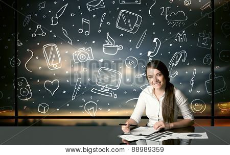 Businesswoman sitting at table with hand drawn social media icons and symbols