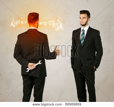 Angry businessman hiding a weapon behind his back