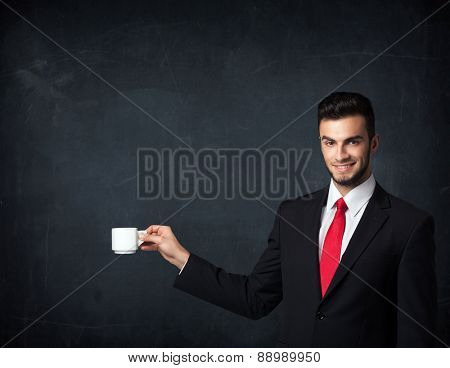 Businessman standing and holding a white cup on a black background