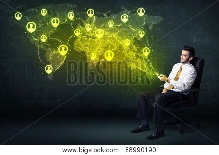 Businessman in office with tablet and social network world map concept on background