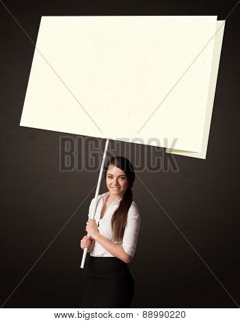 Young businesswoman holding a big, white post-it paper