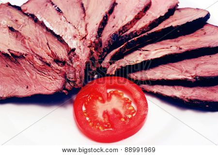 grilled beef meat steak with fried potatoes and tomatoes on white plate isolated over white