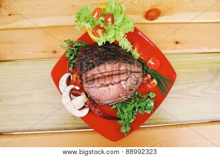 grilled beef sliced on red plate over wood
