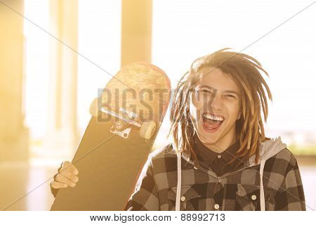 Lifestyle Concept Of Young Guy  With Skateboard And Rasta Hair Warm Filter Applied