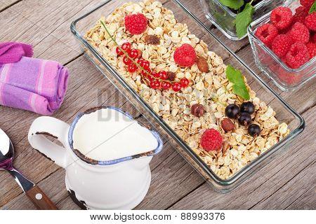 Healthy breakfast with muesli, milk and berries. On wooden table