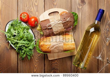Two sandwiches, salad and white wine on wooden table. Top view
