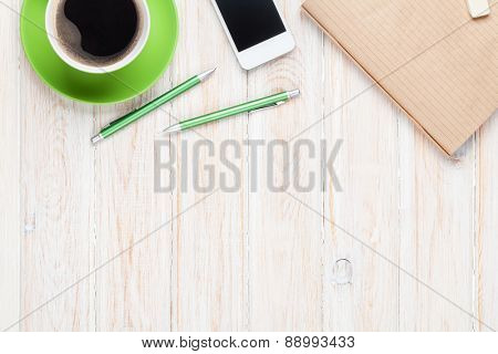 Office desk table with supplies and coffee cup. Top view with copy space