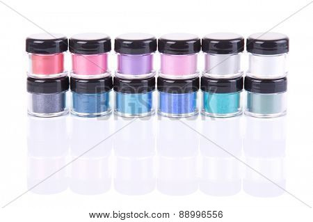 Stack of loose eye shadows in plastic jars, isolated on white background with natural reflection
