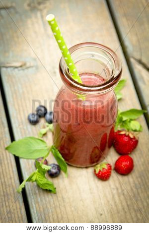 Top view of a berry smoothie with fresh fruits and mint on a rustic wood