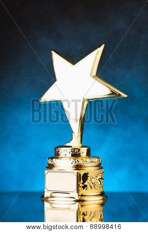 gold star trophy against blue particles background