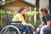 stock photo of rollator  - girl on a wheelchair is talking to a boy in the park - JPG