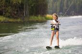 stock photo of ski boat  - Young Waterskier water skiing on a beautiful scenic lake  - JPG
