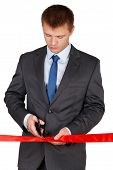 foto of pompous  - Businessman in suit cutting red ribbon with pair of scissors isolated on white background - JPG