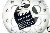 stock photo of mm  - Original old big movie reel for 35 mm cinema projector loaded with film with clapper board on neutral background - JPG