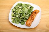 image of caesar salad  - A fresh caesar salad on a square white plate with baked salmon - JPG