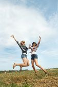 image of freezing  - Freeze frame photography captures happy jumping of two friends in summer farm field - JPG