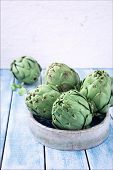 picture of artichoke hearts  - Group of the European artichokes in a ceramic bowl on the table blue in a still - JPG