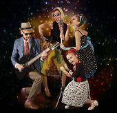 pic of rockabilly  - Rockabilly family band playing music and singing on a black background with glowing lights - JPG