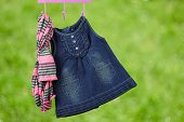 pic of habilis  - Fashion baby dresses hanging on a hanger on a green background - JPG