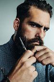 image of grooming  - Brutal Man Grooming His Beard With Scissors - JPG