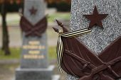 Постер, плакат: Red star and the Ribbon of Saint George at the Soviet War Memorial with graves of Soviet soldiers fa