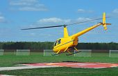 stock photo of helicopters  - Small yellow helicopter taking off from jack - JPG