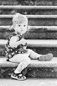 picture of stepping stones  - Little cute girl in sitting on the stairs with stone steps ( black and white )